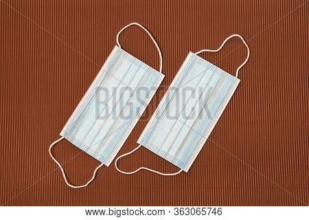 Surgical Protective Masks On A Brown Background. Covid19 Or Coronavirus Prevention.