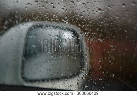 The Car Window Is Wet With Raindrops. Through The Windshield View Of The Road And Side Mirrors In Th