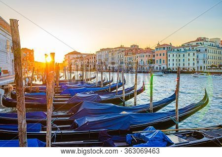 Gondolas Moored Docked On Pier Of Grand Canal Water In Venice City. Baroque Style Colorful Buildings