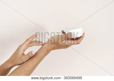 Cropped View Of Young Adult Woman With Pampering Cream Touching Soft Skin On Hands Isolated On White