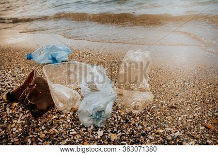 Rubbish Plastic Disposable Bottles  Abandoned On Sandy Beach Around The Sea . Plastic Waste Pollutio