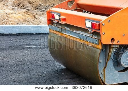 The Metal Cylinder Of A Large Vibratory Roller Powerfully Tamps The Fresh Asphalt Of The Road Surfac