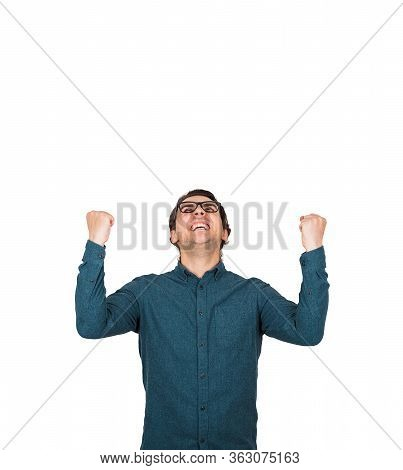 Thankful And Pleased Businessman Keeps Fists Raised Up, Looking Contented Upwards Isolated On White