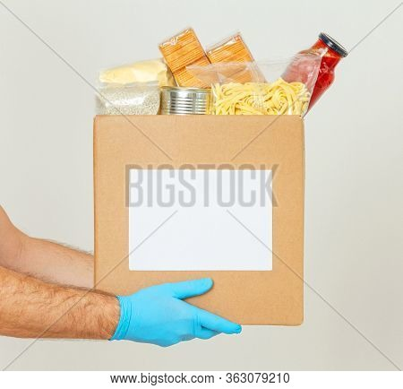 Coronavirus Donation Box. Delivery Food. Volunteer. Food Help. A Mens Hands In Medical Gloves Holds