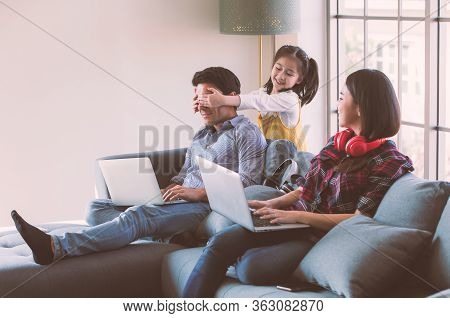 Members Of Diverse Family, Caucasian Father And Asian Mother Using Laptop Computer Notebook To Work