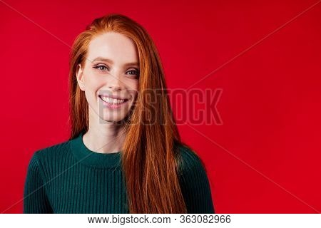 Redhair Ginger Woman In Green Warm Knitted Wool Turtleneck In Red Background Studio