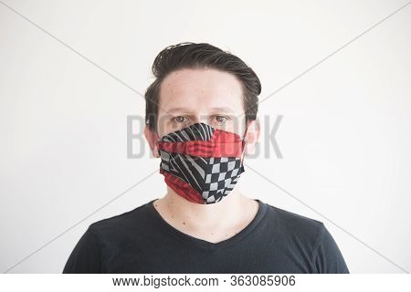 Front Portrait Of A Young Man Wearing A Homemade Reusable Fabric Face Mask, To Prevent The Spread Of