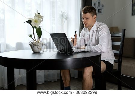 Man With No Pants Using Laptop For Online Video Conference Call From Home