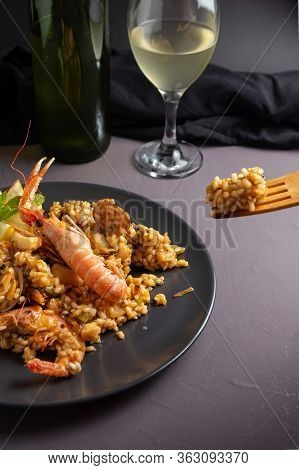 Spanish Seafood Paella On Black Plate, Wooden Fork Taking Paella