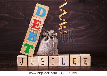 Debt Jubilee Spelled In Letters On Bag And Wooden Blocks And Band Against Brown Background. The Conc