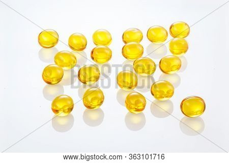 Yellow Gel Capsules Pills. Capsules With Yellow Medicine On Isolated White Background. A Lot Of Caps