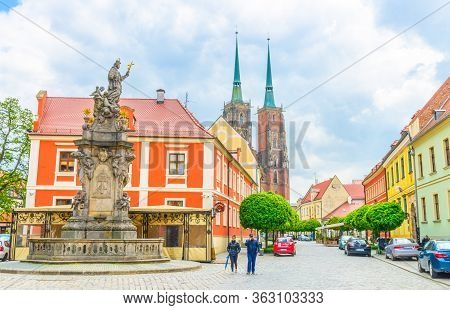 Wroclaw, Poland, May 7, 2019: Monument On Square And Cobblestone Road Street With Green Trees To Cat