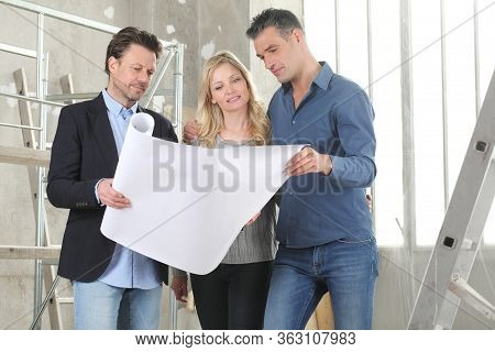 Architect Showing House Design Plans To A Young Couple. House Building Goal Concept. Meeting At Inte