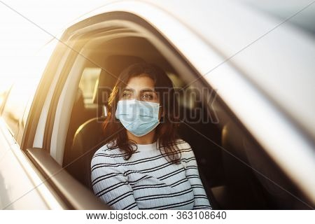 A Woman Wearing A Medical Sterile Mask In A Taxi Car On A Backseat Looking Sideway Out Of Open Windo