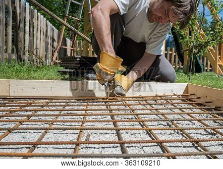 Low Angle View Of A Man Making A Net Of Steel Bars By Clipping Them Together With A Wire And Pliers