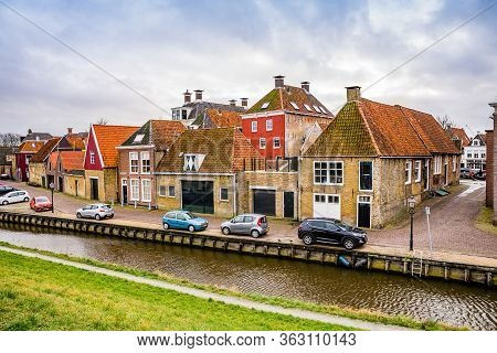 Harlingen, Netherlands - January 10, 2020. Zoutsloot Steet With Water Canal With Traditional Dutch H
