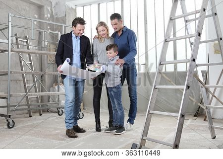 Architect Showing House Design Plans To A Family With Child. Meeting At Interior Construction Site T