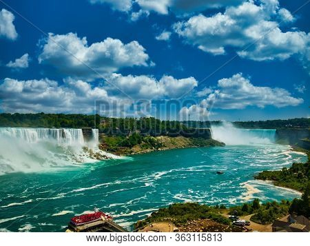 Niagara Horseshoe Falls On Sunny Day And Beautiful Turquoise Waters With Boat Ready To Take Off. Day