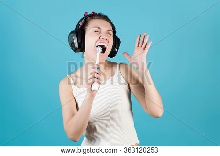 Girl In Headphones Sings In A Toothbrush While Brushing Teeth On A Blue Background