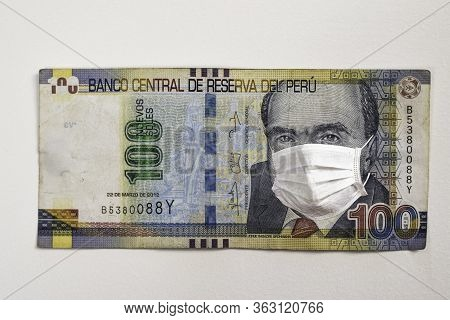 Concept: Quarantine In Peru, 100 Soles Banknote With Face Mask. Economy And Financial Markets Affect