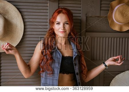 A Woman With Red Hair Poses Against A Wall With Her Arms Outstretched.