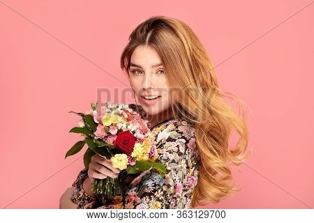 Smiling Woman With Flowers In Hand