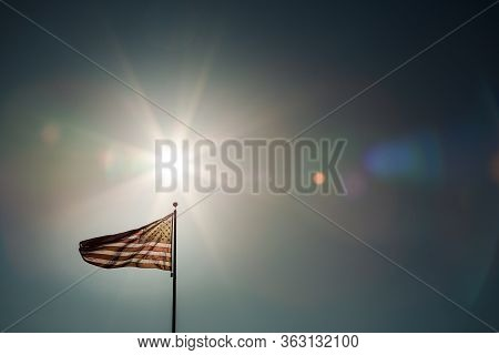A Simple Composition Of An American Flag Flying Backlit With A Sunburst.
