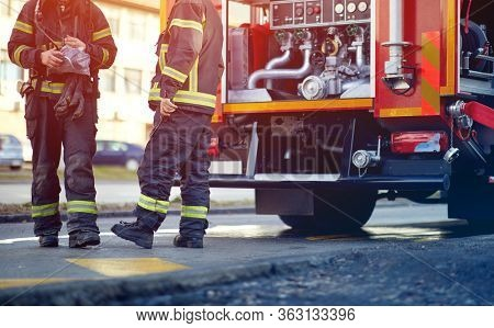 Profesional Fire truck with fire fighting equipment and firemen in protective clothing, helmets and mask.