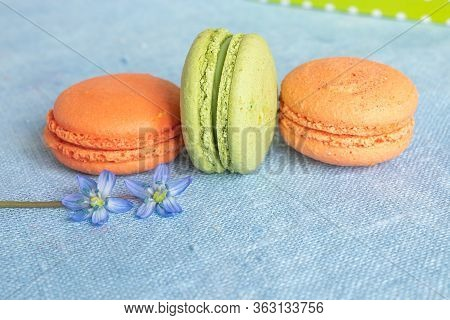 Peach And Pistachio Macaroons And Spring Flower On A Linen Napkin. Macarons Or Macaroons Is French O
