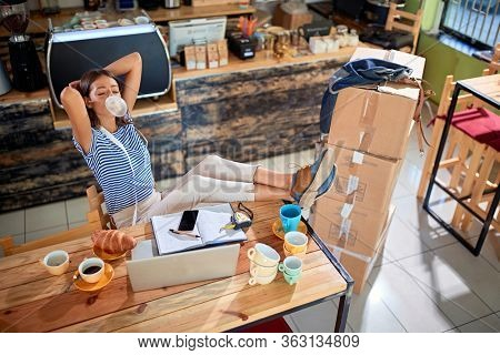 relaxed female making bubble from a gum with her legs on the table and hands behind her head. casual, relaxed, break, pause