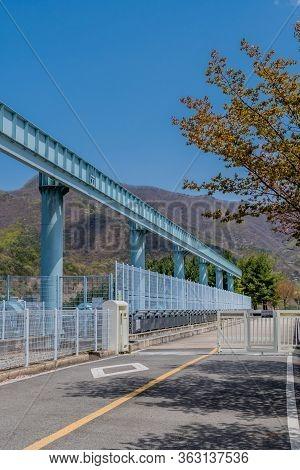 Jinan, South Korea; April 21, 2020: Road Across Yongdam Dam And Spillway Under Blue Sky.