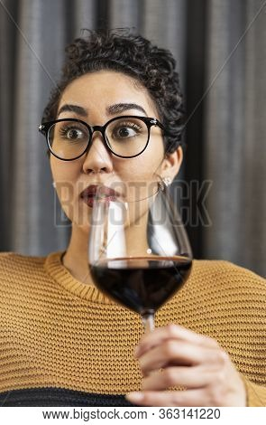 A Woman Wearing Glasses And A Sweater With A Surprised Expression