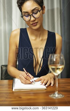 A Woman Wearing Glasses Sits At A Table Drinking White Wine And Writing In A Journal