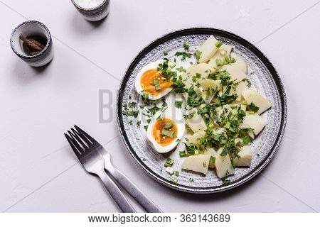 Boiled Potatoes With Herbs And Soft-boiled Eggs In A Plate On Grey Concrete Background. Selective Fo