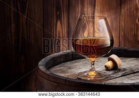 Brandy Or Cognac In Snifter Glass On Old Wooden Barrel As Table