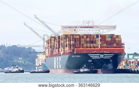Oakland, Ca - Apr 16, 2020: Multiple Tugboats Working In Tandem Assist Cargo Ship Msc Anna To Dock A
