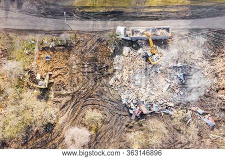 Yellow Excavator Loading Dump Truck At Demolishing Site. Aerial Top View