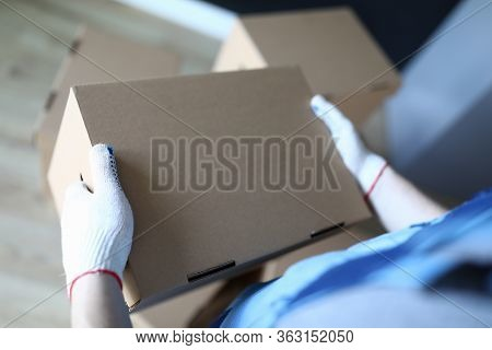 Close-up Loader In Gloves Holds Cardboard Box. Neatly Pack Personal Items. Specialist Carry Out Relo