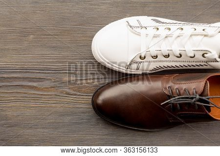 Men's Classic Brown Shoes And White Sneakers On A Wooden Background. Top View