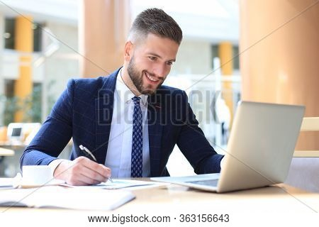Portrait Of Young Man Sitting At His Desk In The Office.