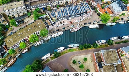 Aerial Drone View Of Delft Town Cityscape From Above, Typical Dutch City Skyline With Canals And Hou