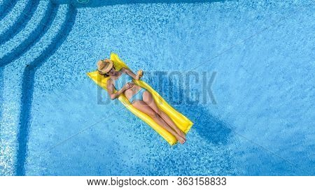Beautiful Young Girl Relaxing In Swimming Pool, Woman Swims On Inflatable Mattress And Has Fun In Wa
