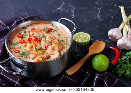 Close-up Of Tom Yum Soup, Tom Kha Soup In A Saucepan On A Concrete Table With Brown Cloth And Spoon,