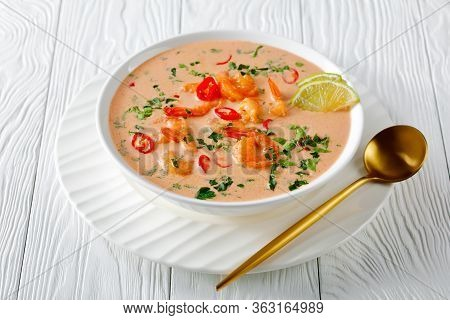 Close-up Of Tom Yum Soup, Tom Kha Soup In A White Bowl On A Wooden Table, Horizontal View From Above