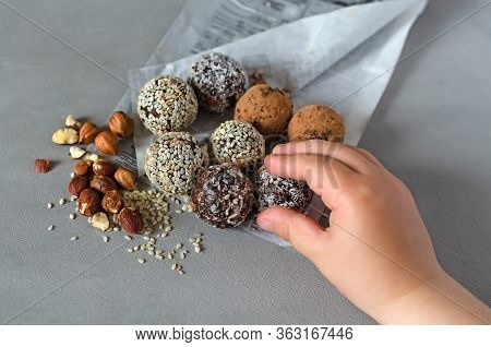 The Child Holds In His Hand The Energy Bols - Homemad Raw Candy. Mixed Dates, Nuts, Dried Fruits, Sp