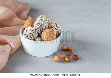 Vegan Energy Balls In A Bowl With Hazelnuts On A Gray Background. Natural Sweets From Nuts And Dried