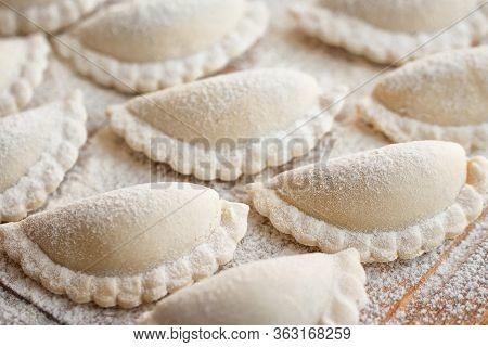 Raw Dumplings On A Wooden Board. The Process Of Making Dumplings. Traditional Homemade Food.  Slavic