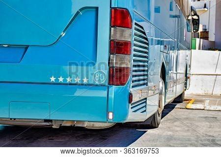 Rear Side Of A Parked Light Blue Coach