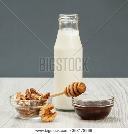 Glass Bottle Of Yogurt, Walnuts And Honey. Health Remedy Foods And Drink For Cold And Flu Relief. Fo
