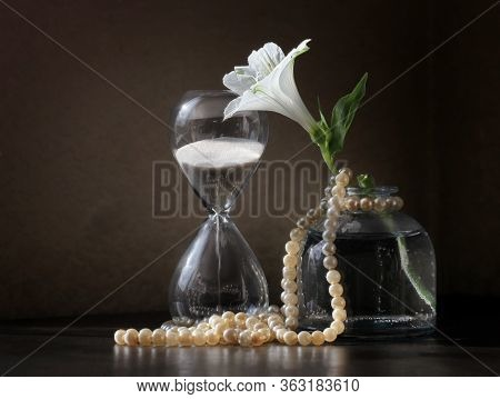 Retro Style Still Life With Vintage Sandglass, Alstroemeria Flower In The Small Bottle And String Of